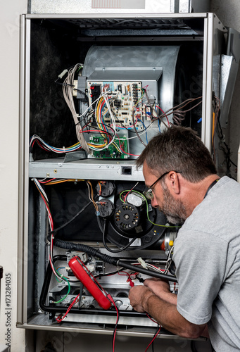 Valokuva Master technician works on a home furnace with volt meter