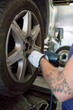 tyre repairer fixing a wheel using an impact wrench