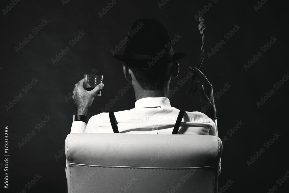 Fototapeta an unidentified man in a suit and hat with a cigar and whiskey staring into the distance. View from the back. The man is a mafia. Millionaire gangster businessman boss