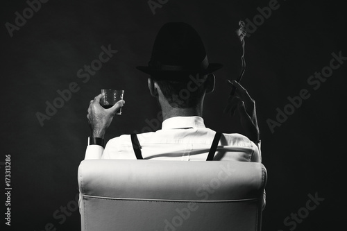 Tablou Canvas an unidentified man in a suit and hat with a cigar and whiskey staring into the distance