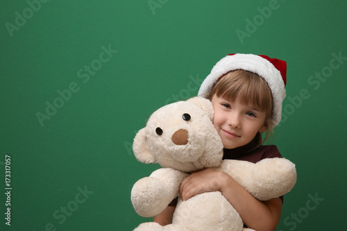 Cute little girl with toy on color background. Christmas concept