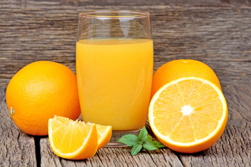 Glass with orange juice on table