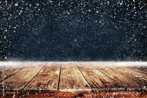 christmas and new year background with wooden deck table and snowfall empty display for product