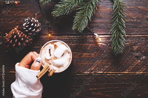 Foto op Plexiglas Chocolade Christmas background - Girl hand holding cup of hot chocolate on wood table with rustic decoration and copy space, flat lay, top view. vintage color tone style.