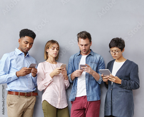 Modern education and technology concept. Diverse students use contemporary tablet and smart phones, look attentively, read information for exam. Addicted mixed race people work in company, use gadgets
