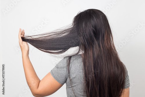 Fototapeta  woman holding messy damaged dry hair in hands