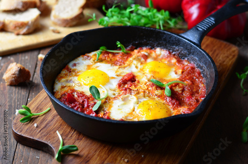 Shakshuka, Fried Eggs with Tomato Sauce in a Pan, Rustic Style and Wooden Background