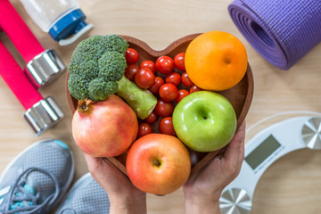 Healthy lifestyle concept, eating clean food good health dietary in heart dish with sporty gym aerobic body exercise workout training class equipment, weight scale and sports shoes in fitness center