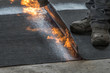 canvas print picture - Professional installation of the waterproofing on the concrete foundation. Installation with rolls of bituminous sealing membrane by heating and melting of bitumen rolls by torch to flame while sealin