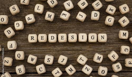 Obraz na plátně Word REDESIGN written on wood block