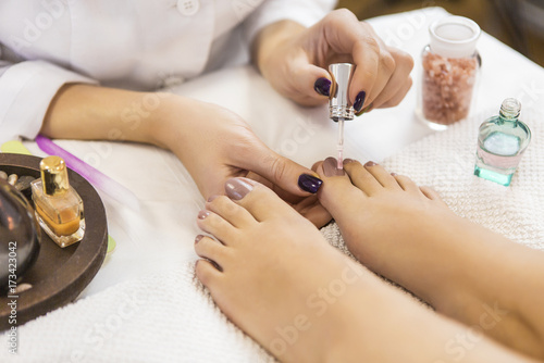 Pedicure at beauty salon. Nail polishing. Close up.