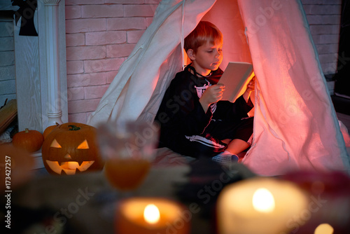 Concentrated cute boy dressed as skeleton sitting inside of teepee and reading interesting book alone in dark room during Halloween night