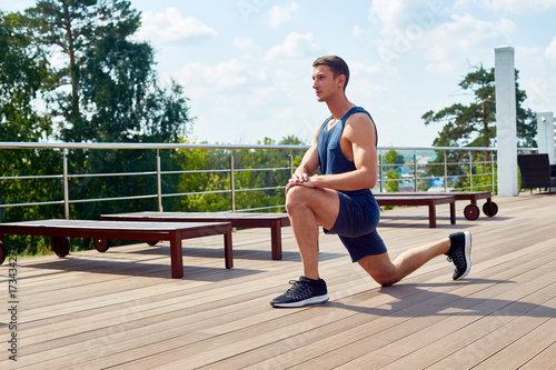 Tablou Canvas Sporty young man doing forward lunge and enjoying picturesque view while having