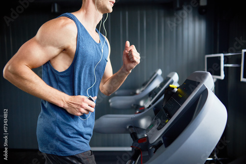 Fotografiet  Unrecognizable muscular man in headphones enjoying favorite song while running o