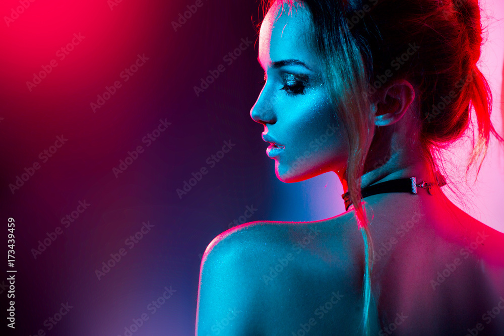 Fototapeta Beautiful sexy girl with trendy make-up in colorful bright lights