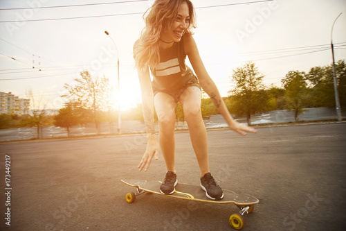 Fotografie, Obraz  Beautiful young girl with tattoos riding longboard in sunny weather