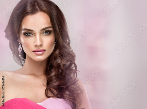 Photo  Brunette girl with long and volume shiny wavy hair in the gentle pink moire
