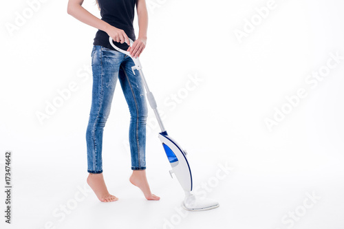 Fototapeta Young woman cleaning floor with modern steam cleaner. Isolated image on white obraz