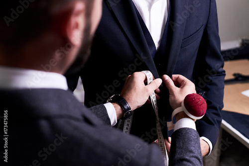 Over shoulder view of bearded fashion designer fitting bespoke suit to model, close-up shot