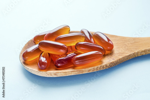 Valokuva Lecithin gel pills in a wooden spoon isolated on a blue light background