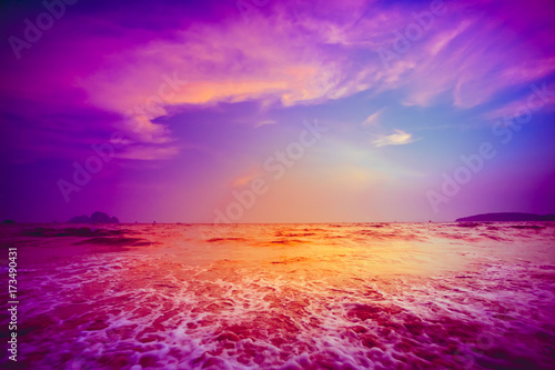 Beautiful tropical sunset in Krabi, Thailand. Dramatic and picturesque evening scene. Ocean waves and colorful cloudy sky in the background. Nature landscape. Travel background. Bright purple toning