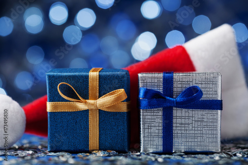 Two christmas gift box or present and santa hat against blue bokeh two christmas gift box or present and santa hat against blue bokeh background magic holiday m4hsunfo