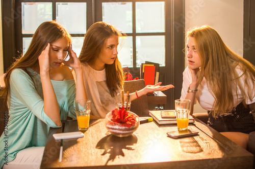 Photo Angry, irritated teenage girlfriends arguing in cafe.