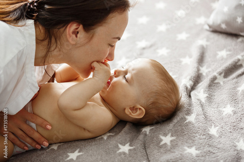 Obraz Close up of happy good looking mother playing with her newborn son, kissing and gently biting his little hands. Happy motherhood concept. - fototapety do salonu