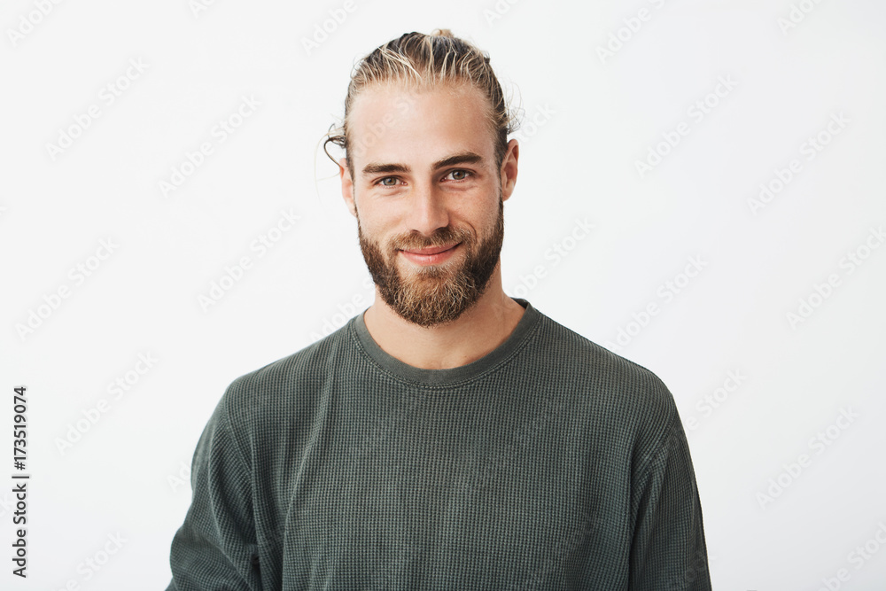 Fototapeta Portrait of beautiful mature blonde bearded guy with trendy hairdo in casual grey shirt smiling and looking in camera.