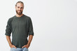 Leinwandbild Motiv Handsome nordic man with beard and stylish hairstyle in grey shirt and jeans smiling, looking in camera, keeps hands in pockets.