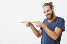 Joyful Mature Guy With Beard Posing For Article In University Newspaper Pointing Aside With Fingers On Both Hands And Smiling.