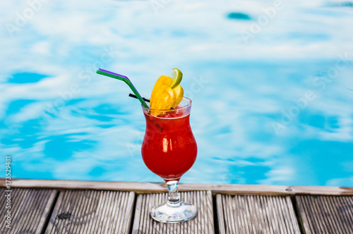 Photo  Glass with coctail with fruits near the pool
