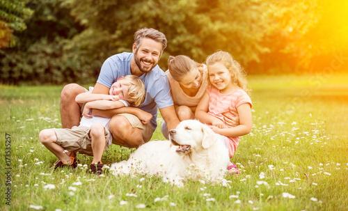 Plakat Rodzina i dzieci z psem w ogrodzie