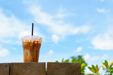 Close Up Of Iced Latte Coffee In Transparent Plastic Glass And Straw With On The Wooden Table With Blue Sky And Cloud. Coffee And Cafe Concept.