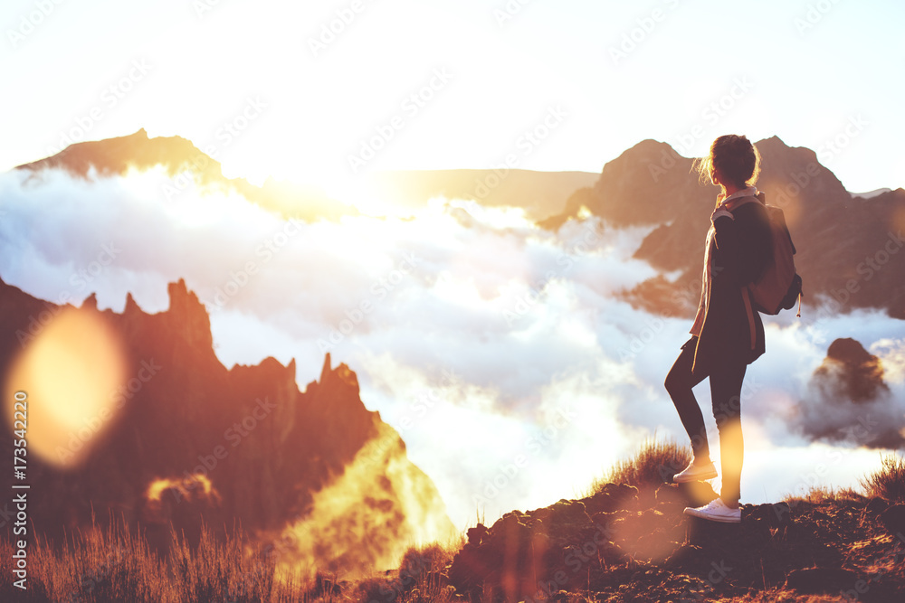 Fototapety, obrazy: Young energetic girl with  backpack standing at edge of cliff in mountains and looking at sunset with a clouds.