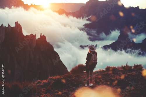 Young curly woman wearing  backpack, sneakers and hat standing on edge of cliff and enjoying landscape, sunset, mountains and clouds.
