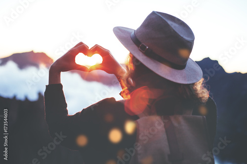 Photo  Young traveler woman with backpack and hat standing on edge of cliff at sunset and making by hands in shape of love heart
