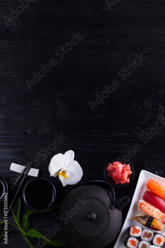 Photo  Japanese sushi dish and tea pot on black wooden background with copy space