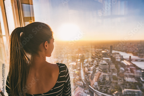 Photo Europe travel woman looking at sunset view of London city skyline from the window of highrise skyscraper tower, famous tourist attraction in the U