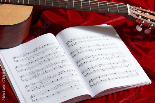 Fototapeta gitara akustyczna i nuty na czerwonym aksamicie tkaniny, Zamknij widok obiektów