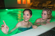 Leinwanddruck Bild - two female friends swimming pool during night time