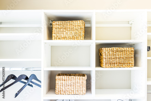 Fotografie, Obraz  Closeup of woven straw baskets in modern minimalist white closet or laundry room