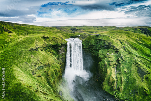 Iceland waterfall Skogafoss in Icelandic nature landscape. Famous tourist attractions and landmarks destination in Icelandic nature landscape on South Iceland. Aerial drone view of top waterfall. - 173631643