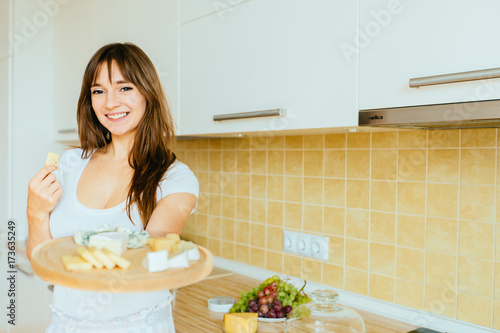 Stampa su Tela  Portraite of smiling brunette woman offers to try a cheese from cheese plate in home kitchen interior background