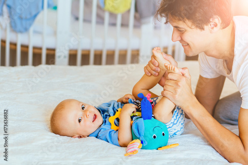 Fototapeta Handsome young father kiss the heels and playing with his infant baby boy, kid looking at camera and smiling obraz na płótnie