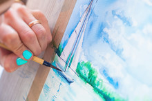 Close-up Young Woman Painter Drawing Watercolor And Wooden Brush On White Paper Seascape With A Single-deck Yacht