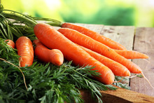 Fresh Organic Carrots With Green Leaves On Wooden Background. Vegetables. Healthy Food