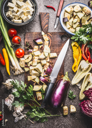Fotografía  Chopped eggplant on wooden cutting board with knife and various vegetarian cooking ingredients for healthy eating , top view