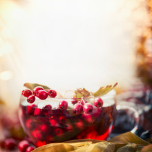 Cup Of Autumn Tea With Red Berries And Leaves At Blurred Fall Nature Background