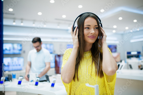 Spoed Foto op Canvas Muziekwinkel Beautiful female listening music, having headphones at tech store. Shopping concept.